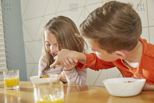Boy and girl sitting at kitchen table, eating breakfast.