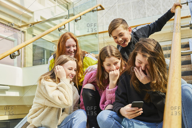 Group of teenage girls in a shopping mall, checking their mobile phones.