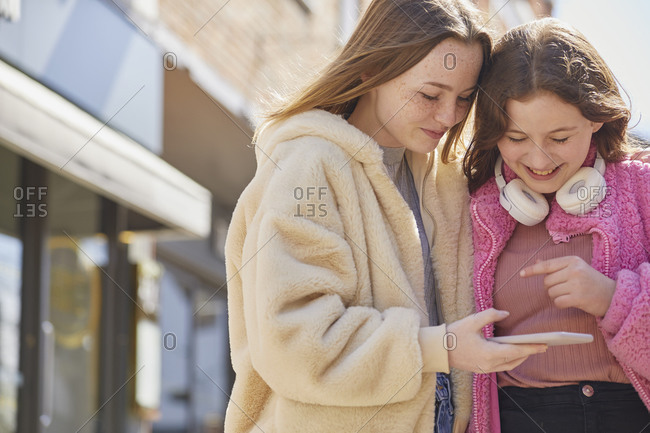 Two teenage girls in a shopping mall, checking their mobile phones.