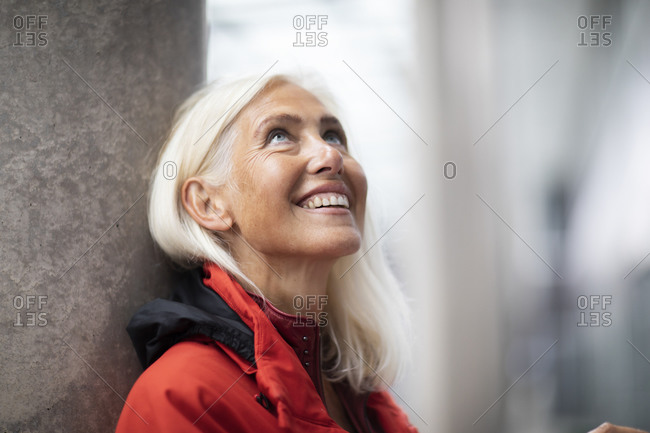 Portrait of smiling woman with long white hair, standing outdoors, looking up.
