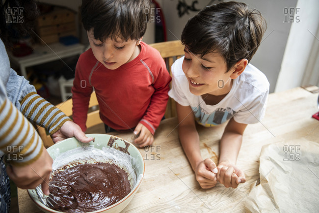 Two boys with black hair sitting at a kitchen table, baking chocolate cake.