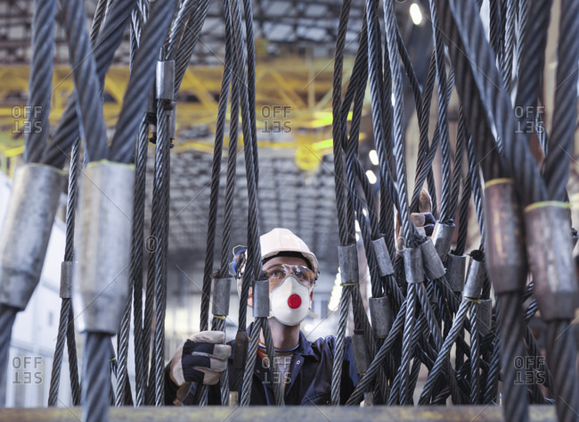 Engineer inspecting lifting cables in turbine repair factory.