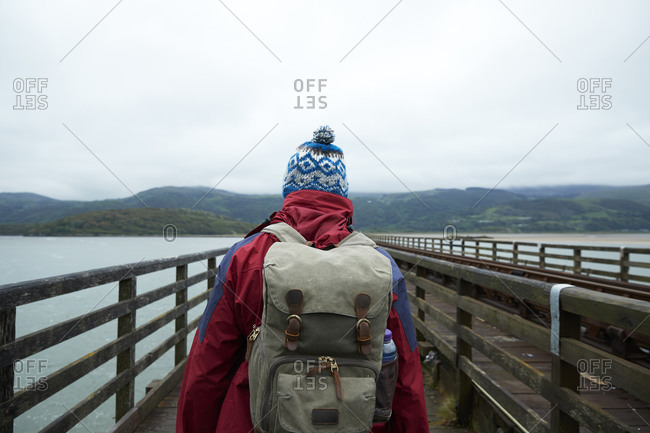 Rear view of hiker walking over Barmouth Bridge, a wooden railway viaduct across the estuary of the River Mawddach, Barmouth