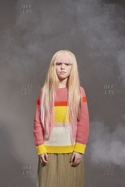 Portrait of girl with long blond hair wearing yellow and red stripe top and khaki skirt, looking at camera, on grey background.