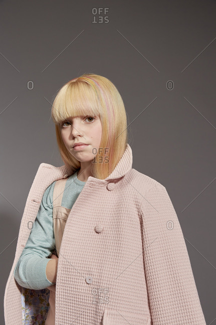 Portrait of girl with long blond hair wearing pale pink coat, looking at camera, on grey background.