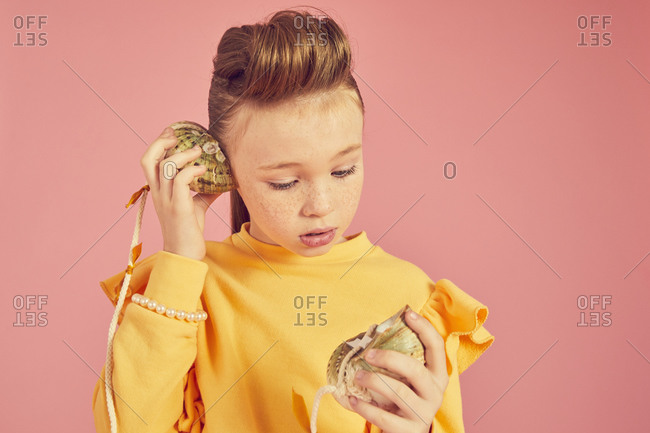 Portrait of brunette girl wearing yellow top, holding sea shell phone, on pink background.