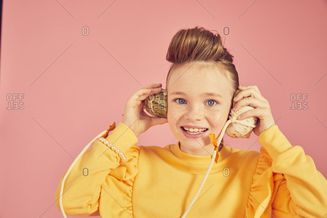 Portrait of brunette girl wearing yellow top, holding sea shell phone, on pink background, looking at camera.