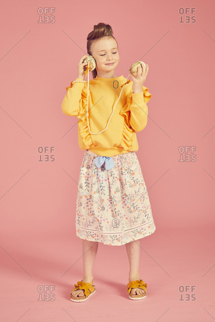 Portrait of brunette girl wearing yellow top and skirt with floral pattern holding sea shell phone, on pink background.