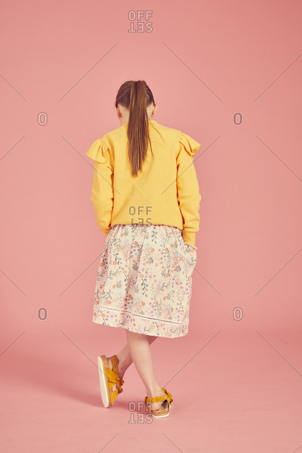 Rear view of brunette girl wearing yellow top and skirt with floral pattern on pink background.