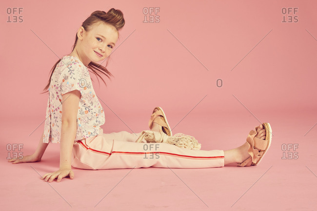 Portrait of brunette girl on pink background, wearing floral top and pale pink trousers sitting on floor, looking at camera.