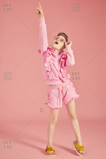 Portrait of brunette girl wearing pink frilly top, shorts and sunglasses on pink background.