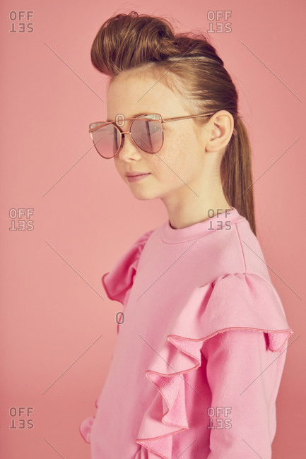 Portrait of brunette girl wearing pink frilly top and sunglasses on pink background.