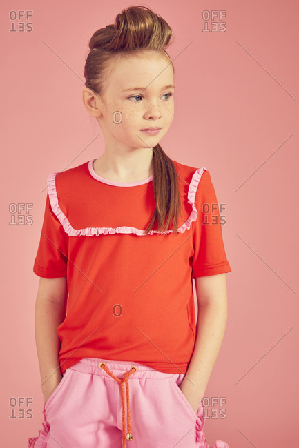 Portrait of brunette girl wearing red T-Shirt on pink background.