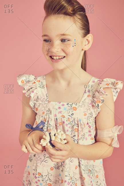 Portrait of smiling brunette girl wearing frilly dress with floral pattern on pink background.