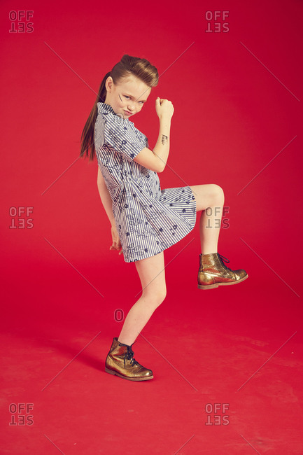 Portrait of brunette girl wearing blue dress and combat boots on red background.