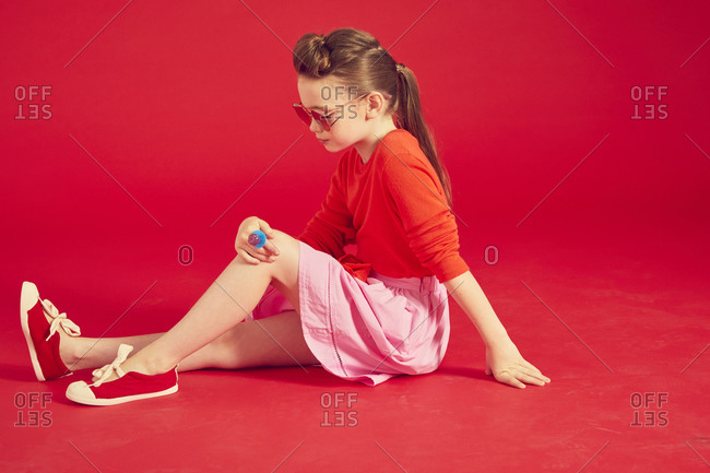 Portrait of brunette girl wearing red T-Shirt and pink skirt sitting on floor, on red background.