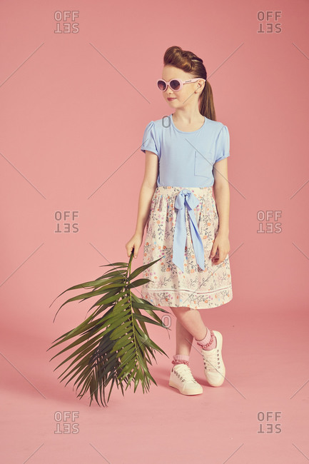 Portrait of brunette girl wearing blue T-Shit and cream skirt with floral pattern, holding palm leaf, on pink background.