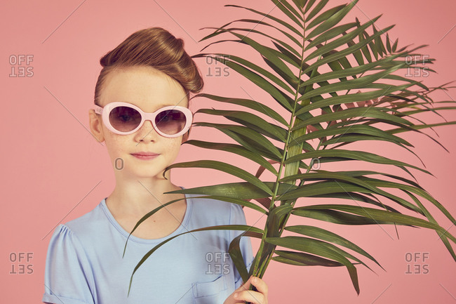 Portrait of brunette girl wearing blue T-shirt and sunglasses on pink background, holding palm leaf, looking at camera.