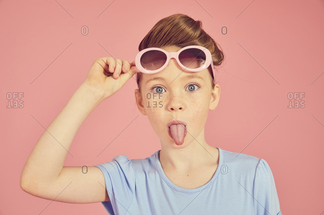 Portrait of brunette girl wearing blue T-shirt and sunglasses on pink background, sticking out tongue at camera.