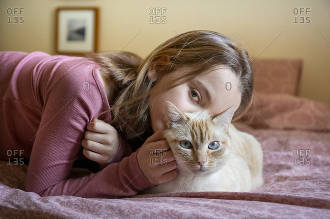 Portrait of girl and white and ginger cat lying on bed.