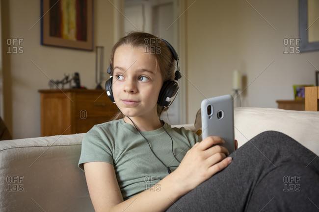 Girl wearing headphones sitting on sofa, holding mobile phone.
