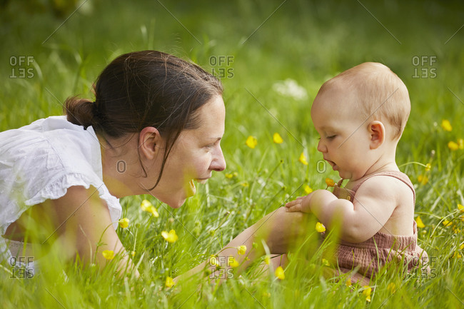 Mother and baby daughter playing in a meadow.