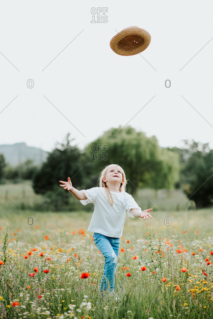 Portrait of young girl with blond hair in a wild flower meadow, throwing straw hat in air.