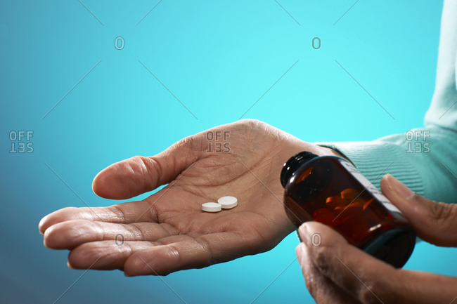 Close up of person holding tablets and brown pill bottle, on blue background.
