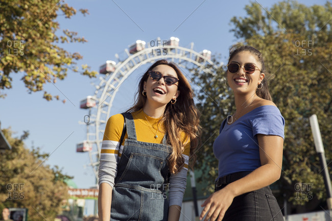 Two young women with long brown hair standing in a park near a Ferris wheel, wearing sunglasses, smiling at camera.
