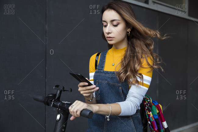 Young woman with long brown hair standing on electric scooter, using mobile phone.
