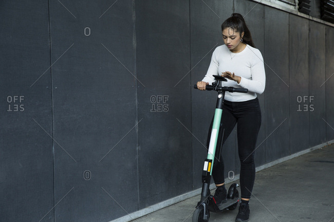 Young woman with long brown hair standing on electric scooter.