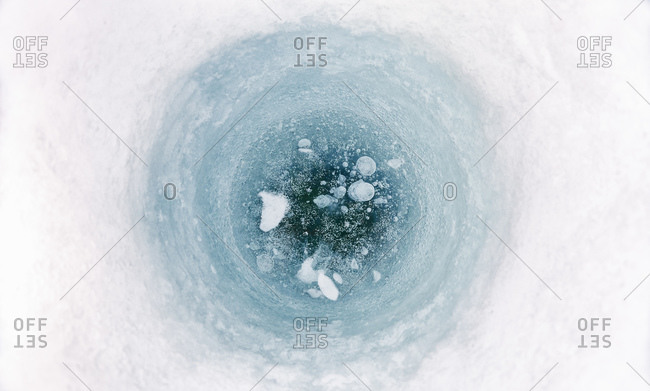 High angle close up of ice-fishing hole on frozen lake in Vasterbottens Lan, Sweden.