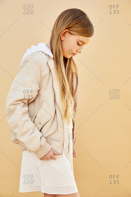 Portrait of girl with long blond hair wearing cream-colored hooded jacket, on pale yellow background.