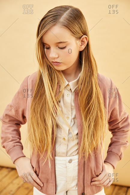 Portrait of girl with long blond hair wearing shorts, shirt and pink jacket, on pale yellow background.