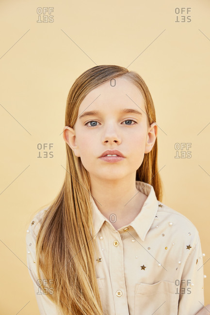 Portrait of girl with long blond hair wearing cream-colored shirt, on pale yellow background.