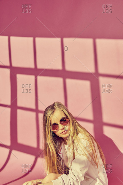 Portrait of girl with long blond hair wearing sunglasses and jacket, on pink background.