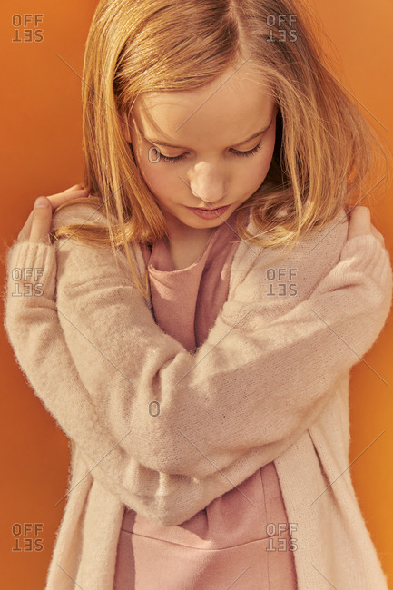 Portrait of girl with long blond hair wearing cream-colored cardigan, on orange background.