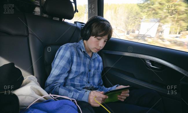 Boy sitting in a car, wearing headphones and holding digital tablet, Vasterbottens Lan, Sweden.