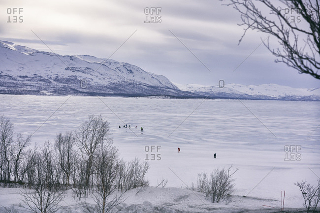 View across frozen lake with people in the distance, Vasterbottens Lan, Sweden.