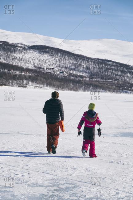 Rear view of two boys walking on frozen lake in Vasterbottens Lan, Sweden.