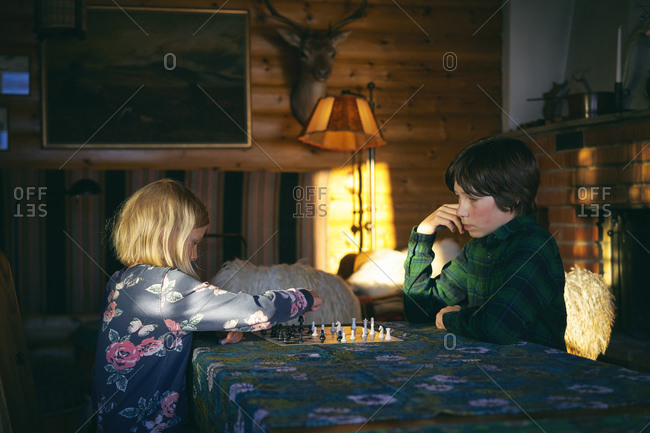 Boy and girl sitting at a table in a log cabin, playing chess, Vasterbottens Lan, Sweden.