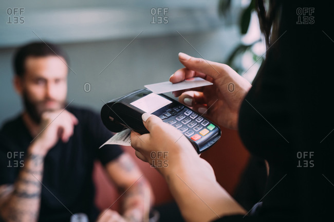 Close up of waitress in a bar, holding card reader and credit card.
