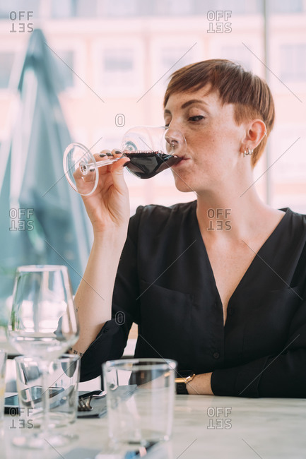 Young woman with short hair wearing black top sitting at table in a bar, drinking red wine.