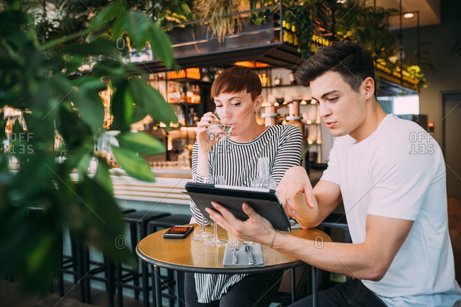 Young woman and man sitting at a table in a bar, looking at digital tablet.