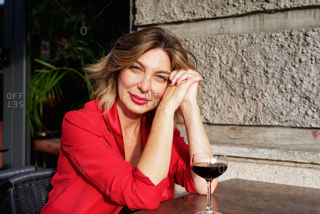 Portrait of seated woman in a red jacket, with a glass of red wine, looking at camera.