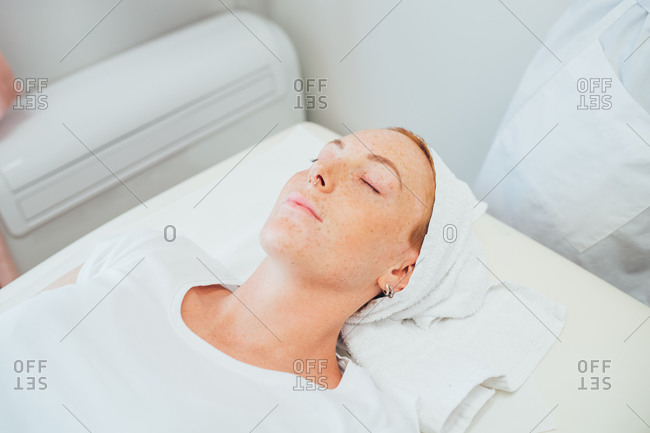 Woman lying on treatment bed in a beauty salon.
