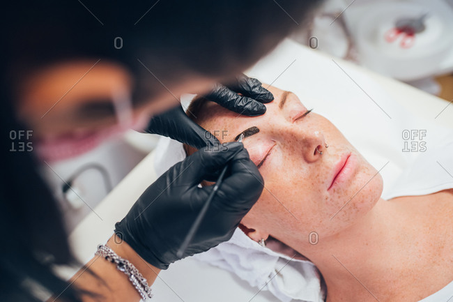 Woman getting her eyebrows done in a beauty salon.