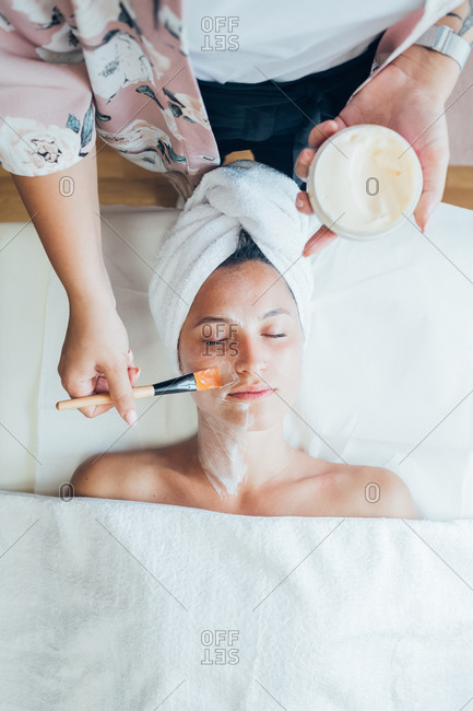 Woman getting a facial treatment in a beauty salon.