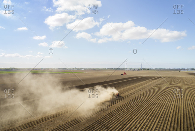 Aerial view of tractor blowing up dust on drought stricken potato field in Netherlands.