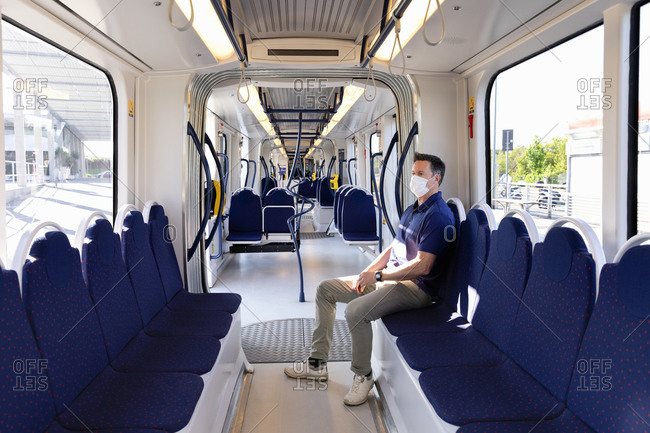 Man wearing face mask sitting in an empty train in Florence, Italy during the Corona virus crisis.